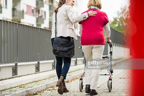Adult granddaughter assisting her grandmother walking with wheeled walker, back view