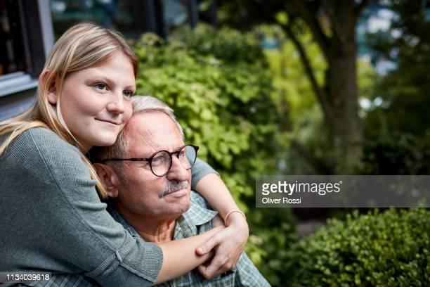 adult granddaughter embracing grandfather in garsden - pareja hombre mayor y mujer joven fotografías e imágenes de stock