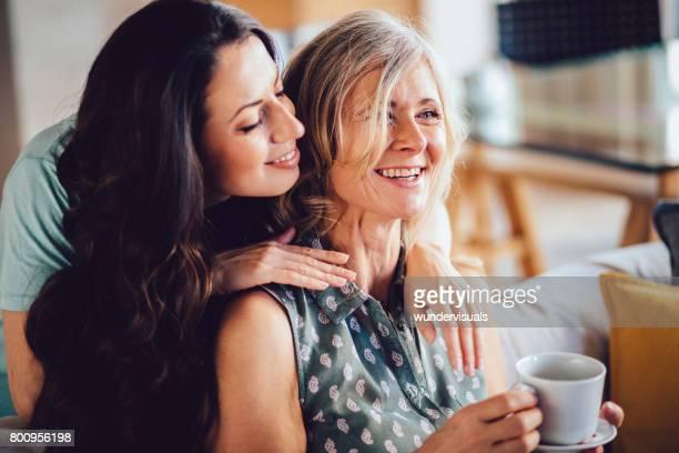 Volwassen kleindochter omhelst grootmoeder terwijl het besteden van tijd samen thuis
