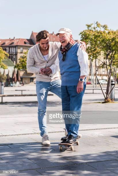 adult grandson assisting senior man on skateboard - jung geblieben stock-fotos und bilder