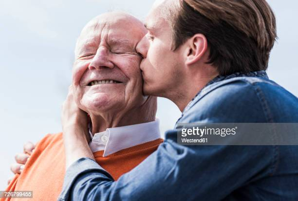 adult grandson kissing senior man outdoors - love emotion fotografías e imágenes de stock