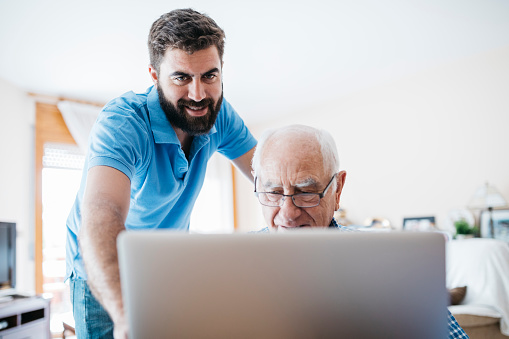 Adult grandson teaching his grandfather to use laptop - gettyimageskorea