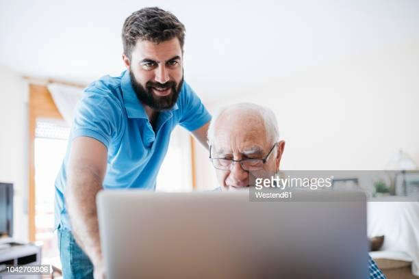 adult grandson teaching his grandfather to use laptop - profesora mayor fotografías e imágenes de stock