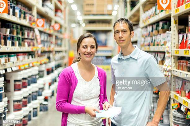 Adult heterosexual couple holding a shopping list and smiling