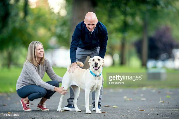 Adult heterosexual couple looking proud as they pet their dog
