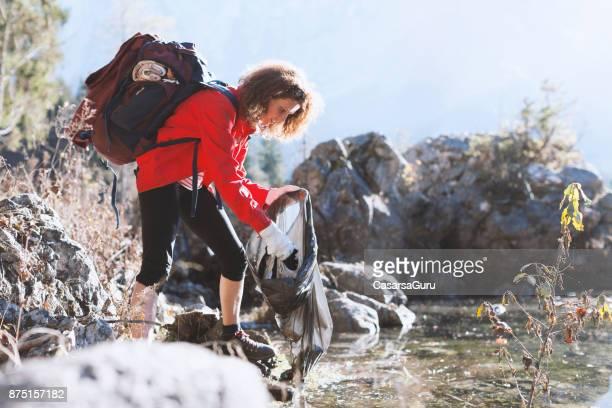 Adult Hiker Picking Up Garbage By a Lake