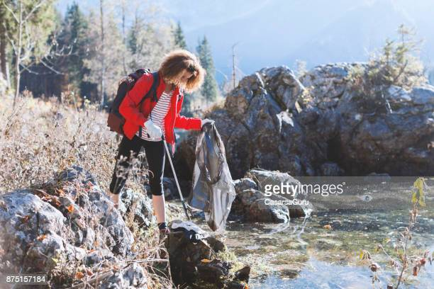 Adult Hiker Picking Up Garbage By a Lake