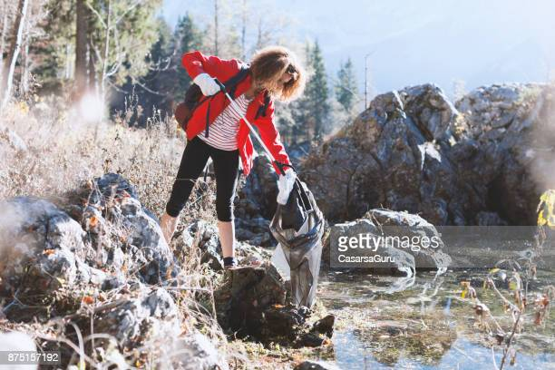 adult hiker picking up garbage by a lake - selfless stock pictures, royalty-free photos & images