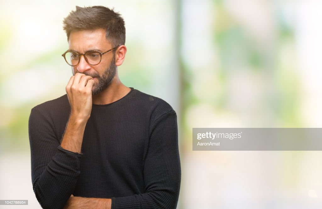 Adult hispanic man wearing glasses over isolated background looking stressed and nervous with hands on mouth biting nails. Anxiety problem. : Stock Photo