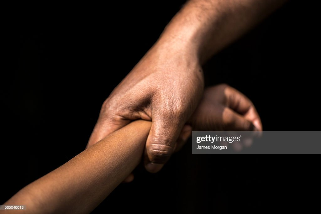 Adult holding a child's wrist : Stock Photo