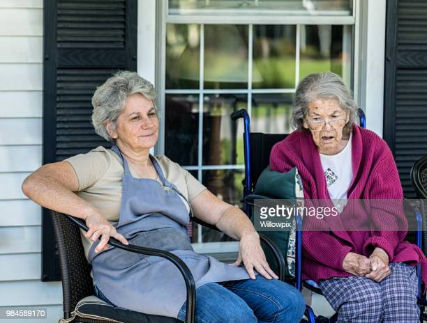 adult home caregiver daughter sitting with elderly mother dementia patient - dementia stock pictures, royalty-free photos & images