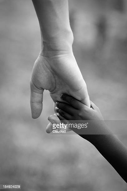 Adult is holding hand of black child