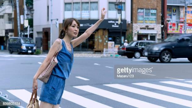 大人の日本女性通りそばに立っていると東京でタクシーを待っています。