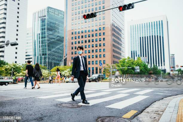 adult korean businessman with face mask crossing the street and keeps social distance - south korea stock pictures, royalty-free photos & images