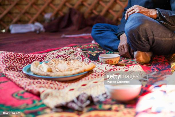 adult kyrgyz man drinking tea inside a yurt, xinjiang, china - kyrgyzstan stock pictures, royalty-free photos & images