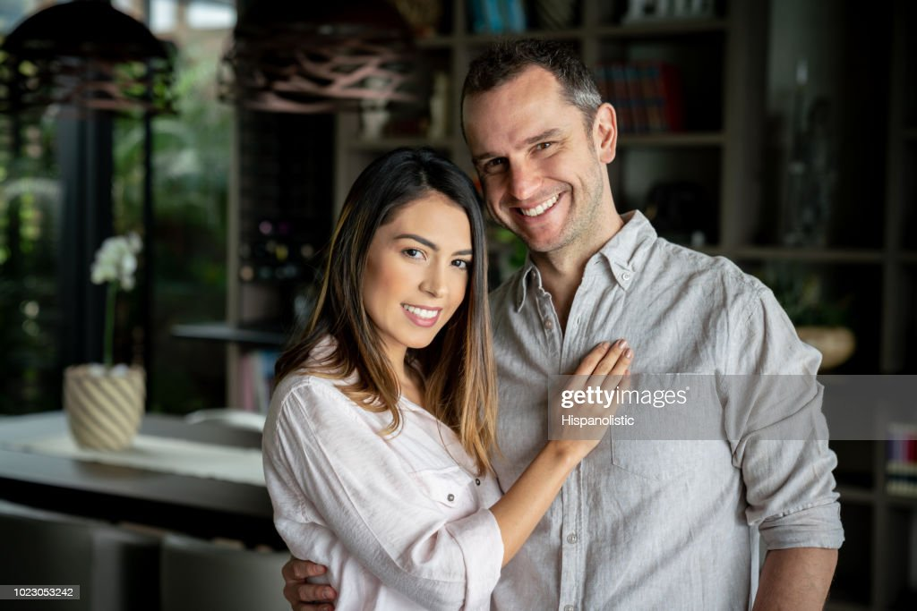 Adult latin american couple at home embracing each other while looking at camera smiling : Stock Photo