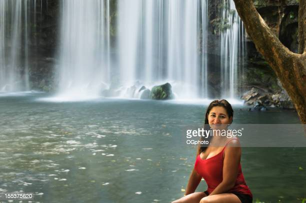 Adult latina woman sitting in front of a waterfall