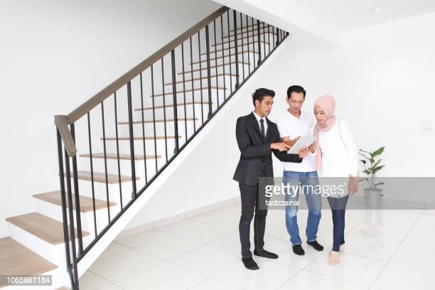 adult malay muslims discussing with real estate agent for house purchase/ rental - muslim couple stock pictures, royalty-free photos & images
