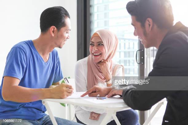 adult malay muslims signing documents for house purchase/ rental - malay stock photos and pictures