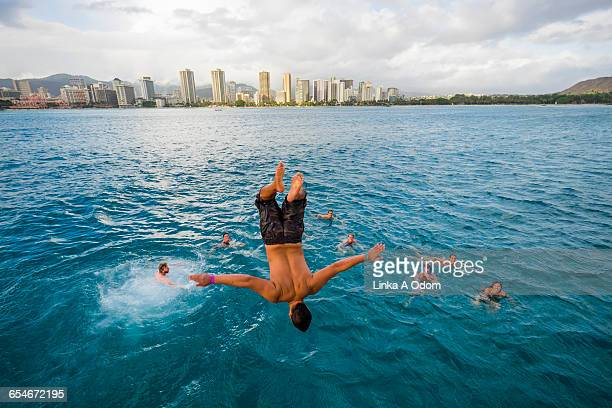adult male backflipping into ocean - tripping falling stock pictures, royalty-free photos & images