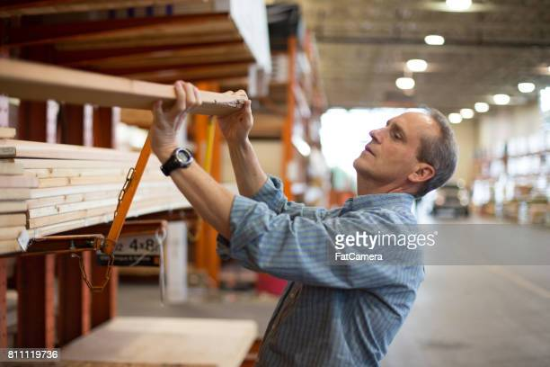 Adult male customer in hardware store choosing lumber