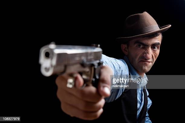 Adult male in hat pointing gun at viewer.