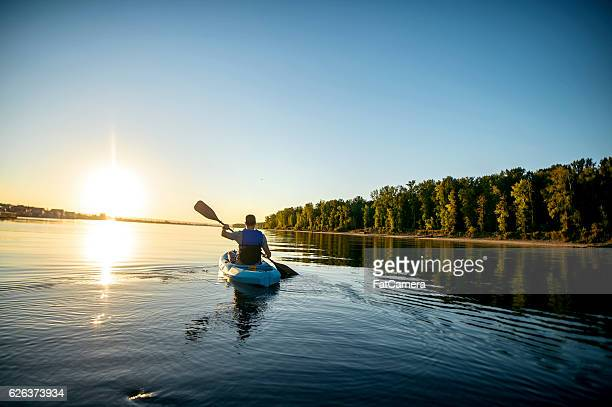 adult male kayaking in a river at sunset - kayak stock pictures, royalty-free photos & images