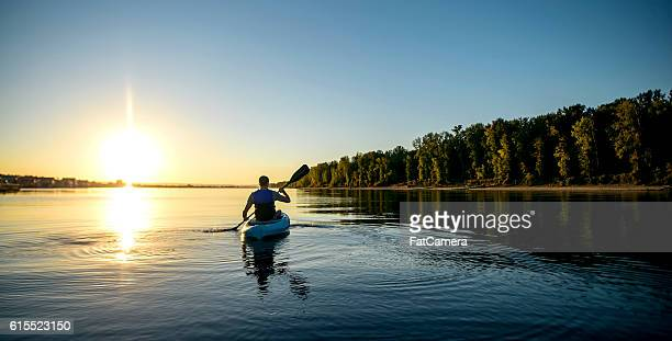 adult male paddling a kayak on a river at sunset - kajak stock-fotos und bilder