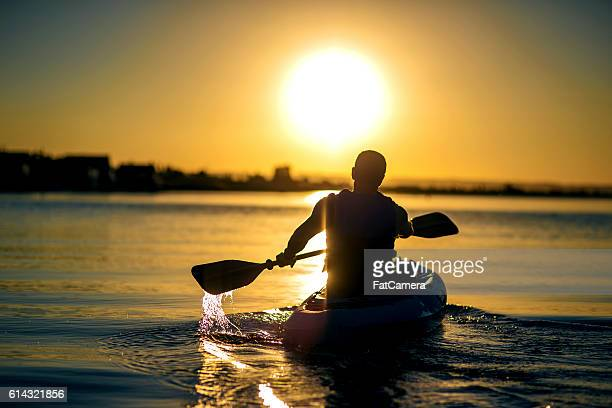 Adult male paddling a kayak on a river into the sunset