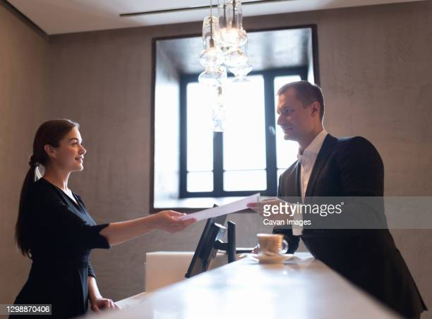 adult male passing receipt of services for checkout on reception in hotel - form filling stock pictures, royalty-free photos & images