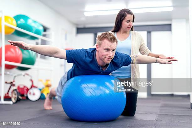 Adult male patient balancing on a therapy exercise ball