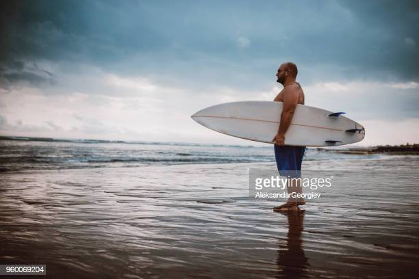 adult male planning to surf in sea indonesia - chubby stock pictures, royalty-free photos & images