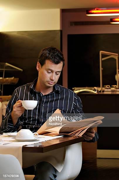Adulto homem ler o jornal durante o pequeno-almoço