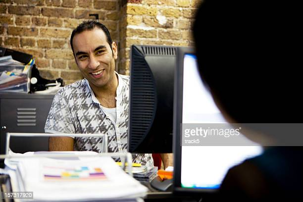 adult male smiling at colleague from behind a computer - handsome pakistani men stock photos and pictures