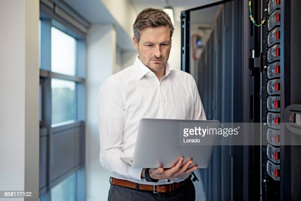 Adult Male Technician Manager working in Server Room Setting