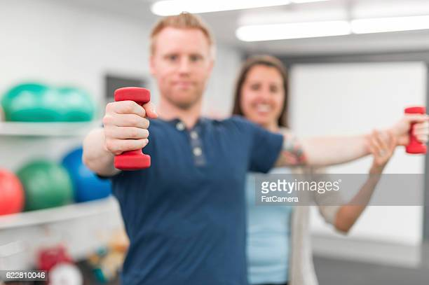 Adult male uses weights for a physcial therapy exercise