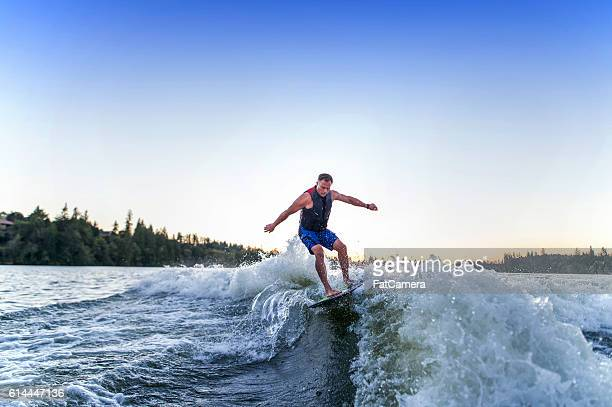Adult male wake surfing behind a ski boat