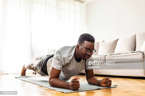 adult male workout in his living room on yoga mat exercising plank position - plank position stock pictures, royalty-free photos & images