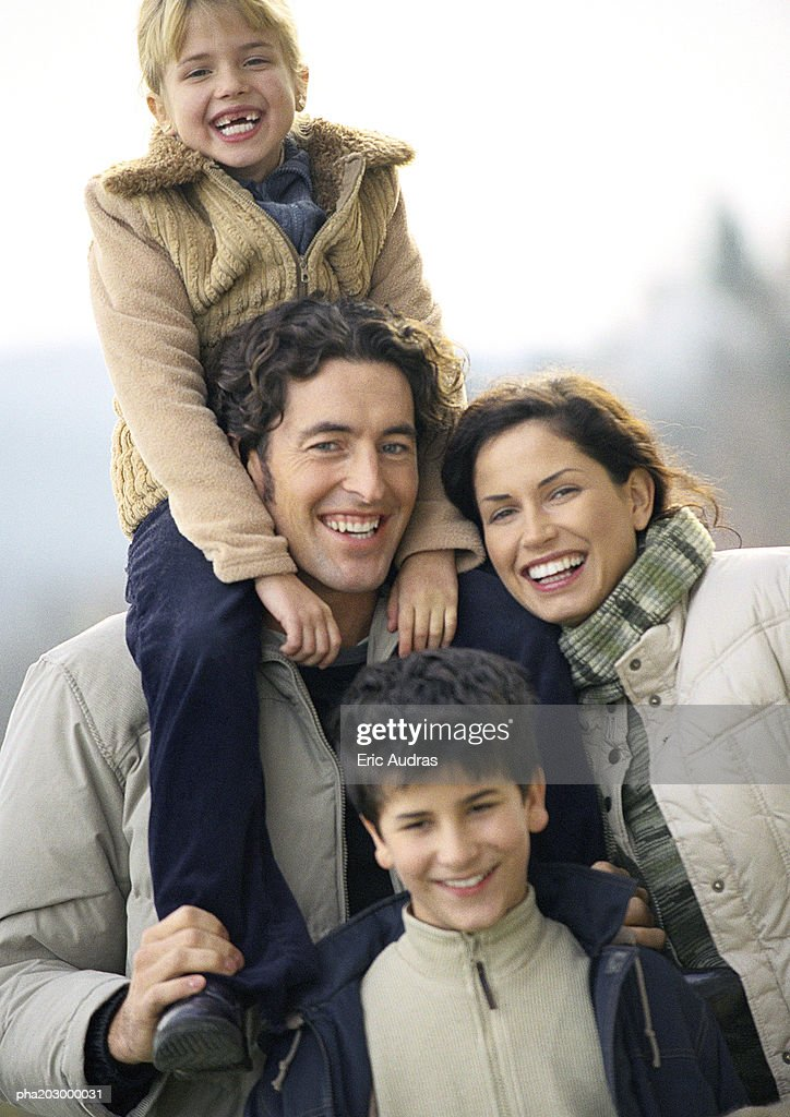 Adult man and woman standing with two children, little girl on man's shoulders, little boy standing in front, portrait : Stockfoto