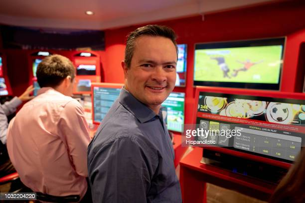 Adult man at the casino betting on live football game looking at camera smiling