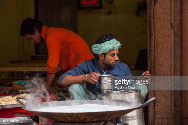 Adult man cook masala milk and watch in your phone. Vrindavan, India