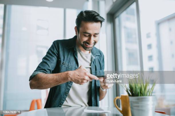 adult man depositing check with smartphone - portable information device stock pictures, royalty-free photos & images