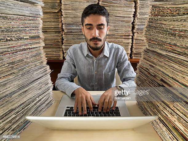 Adult man doing research on computer in newspaper archive