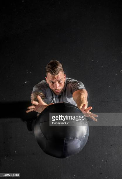 adult man doing strength exercise with medicine ball - concentration stock pictures, royalty-free photos & images