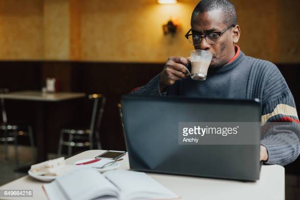 Adult man drinking coffee and surfing the net