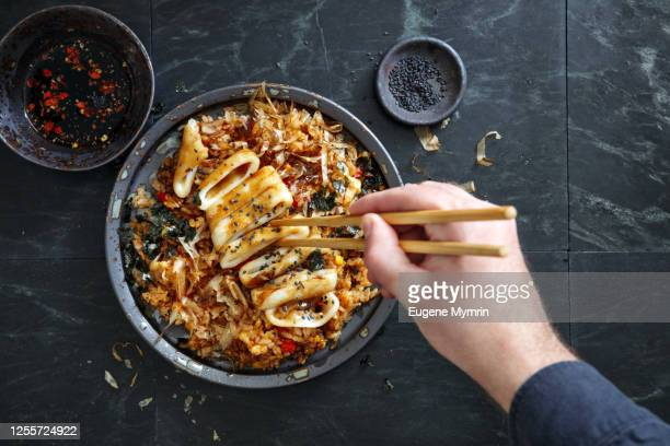 adult man eating japanese grilled squid with teriyaki sauce on topped fried rice bowl - chinese culture stock pictures, royalty-free photos & images