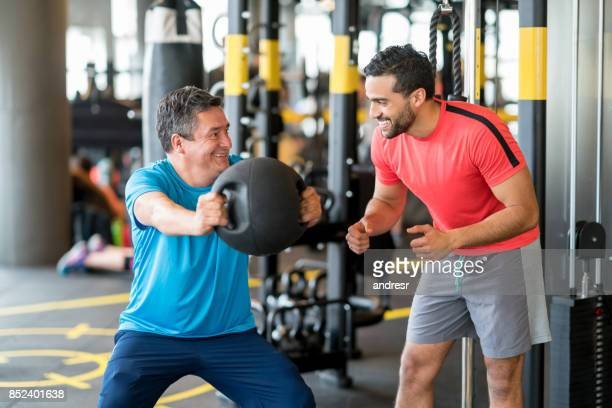Adult man exercising at the gym with a personal trainer