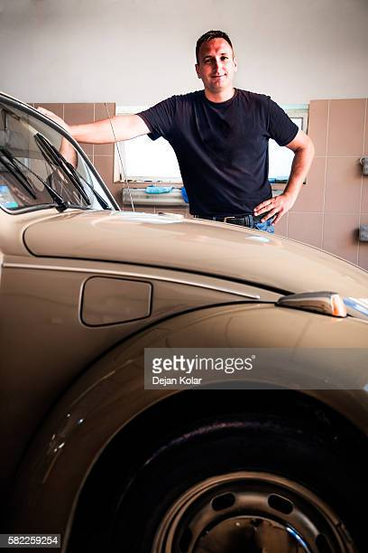 Adult man finished polishing VW beetle in workshop