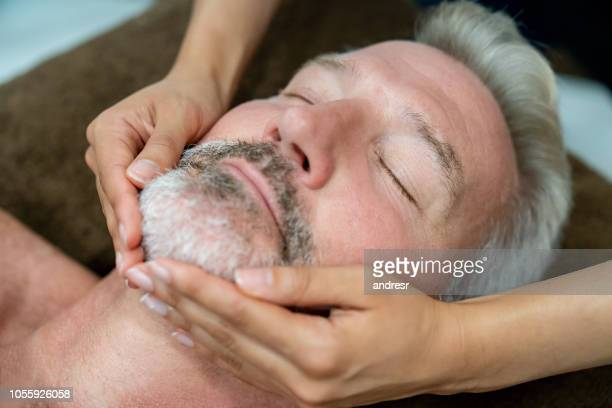 adult man getting a facial massage at a spa - indulgence stock pictures, royalty-free photos & images