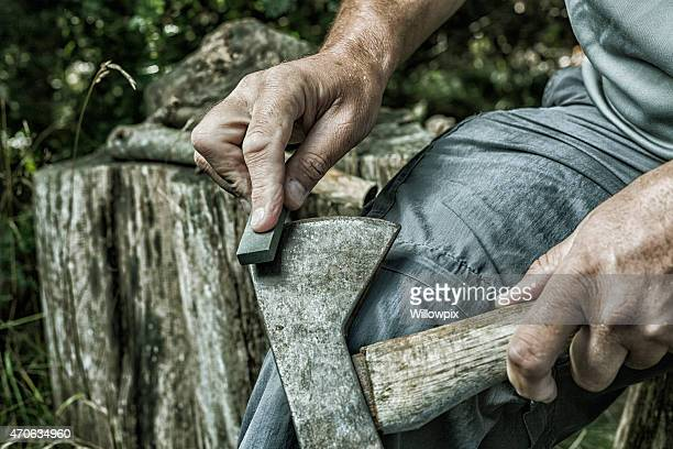 Adult Man Hands Sharpening Rusty Axe with Whetstone